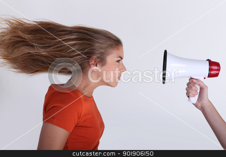Girl with hair blown backwards by megaphone stock photo, Girl with hair blown backwards by megaphone by photography33
