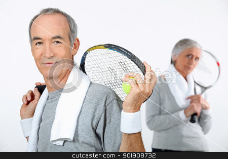 Older couple with tennis rackets stock photo, Older couple with tennis rackets by photography33
