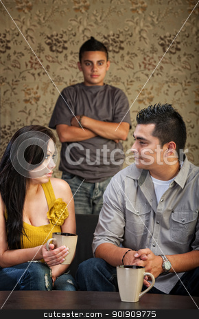Family With Problem Child stock photo, Young Latino family with stubborn son in background by Scott Griessel