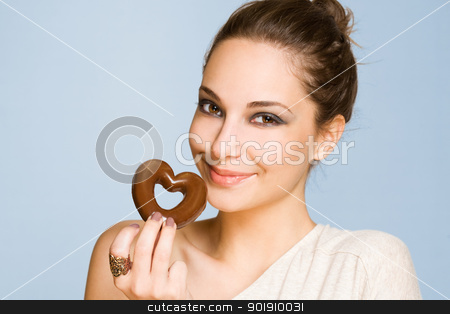 Chocolate love. stock photo, Portrait of a gorgeous happy young brunette woman holding heart shaped cookie. by exvivo