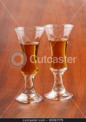Liquor stock photo, Two little glasses with liquor, over wooden background by Fabio Alcini