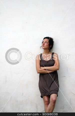 young woman on a plain wall looks pensive stock photo, young woman on a plain wall looks pensive by Tobias Arhelger
