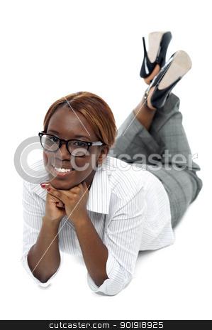 Relaxed african businesswoman lying on floor stock photo, Relaxed african businesswoman lying on floor. Indoor studio shot by Ishay Botbol