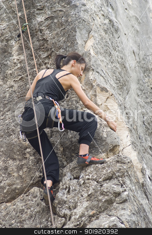 Climbing stock photo, Young woman climbing and stretching and nearly at the summit, on a rock face by Serge VILLA