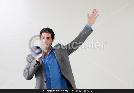 voice up stock photo, Businessman shouting through megaphone by eskaylim