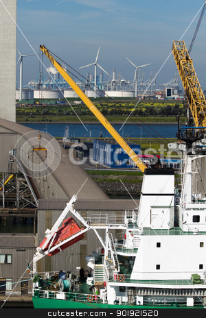 Close up view of ship at terminal stock photo, Close up view of ship at terminal with industrial buildings and windmills in background by Colette Planken-Kooij