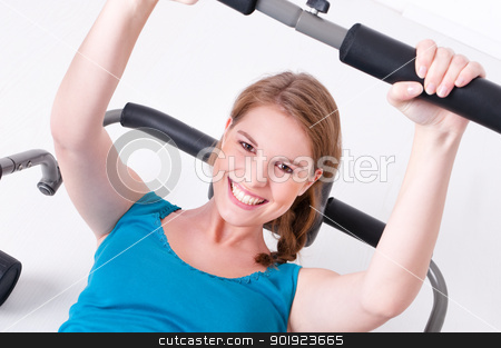Woman in gym stock photo, Young a beautiful woman is doing some sports in a gym by Picturehunter