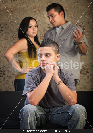 Young Teen Spacing Out stock photo, Young Latino boy in blank stare with concerned parents behind him by Scott Griessel