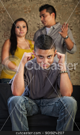 Rude Teenager Plugs Ears stock photo, Grinning Hispanic teenager plugging his ears with frustrated parents by Scott Griessel