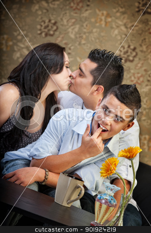 Boy Pretends to Gag While Parents Kiss stock photo, Grossed out child in front of kissing parents by Scott Griessel