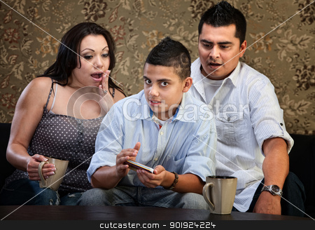 Shocked Parents and Texting Teen stock photo, Shocked parents seeing a male teenagers smartphone by Scott Griessel