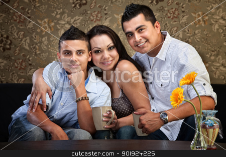 Joyful Hispanic Family stock photo, Happy Latino family hugging each other indoors by Scott Griessel