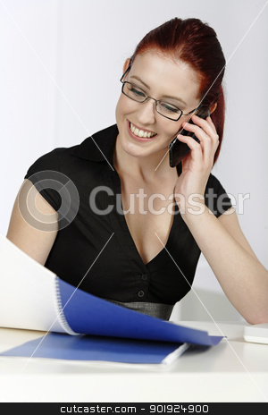 Woman on mobile at work stock photo, Beautiful young woman talking on her mobile phone at work by Gareth Lewis