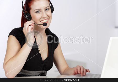 Woman talking on the phone stock photo, Professional woman talking on a headset in her office at work by Gareth Lewis