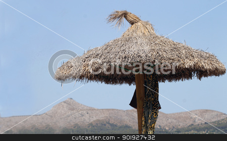 Straw Parasol on beach stock photo, Straw Parasol on beach with mountains in background, Majorca, Spain. by Martin Crowdy