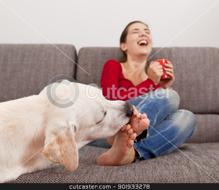 Dog licking the toes stock photo, Woman drinking coffee on the sofa with her dog licking her toes by ikostudio