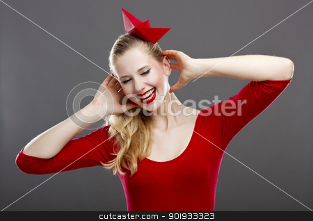 Woman in red stock photo, Beautiful fashion woman in red posing with a paper hat on the head by ikostudio