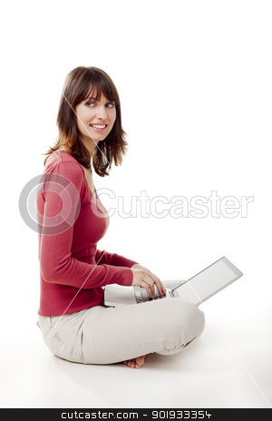 Working with a laptop stock photo, Beautiful woman sitting on the floor and working with a laptop by ikostudio