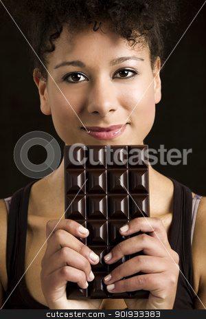 Woman with a chocolate bar stock photo, Beautiful african woman holding a huge dark chocolate bar by ikostudio