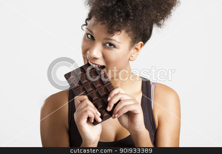 Woman eating chcolate stock photo, Beautiful african woman holding and eating a huge dark chocolate bar by ikostudio