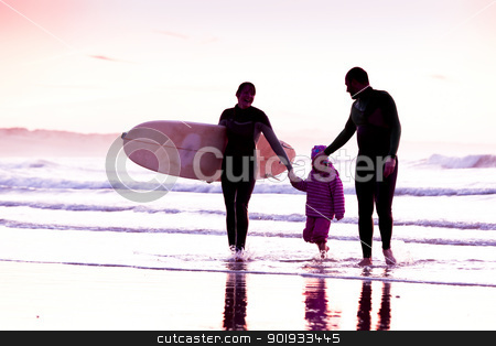 Surftime stock photo, Female surfer and her familly walking in the beach at the sunset by ikostudio