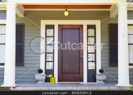 Brown stained Front Door stock photo, Brown stained Front Door on a home with bordering window and a pillared porch by bobkeenan