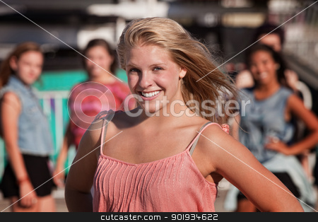 Cheerful Teenage Girl stock photo, Cheerful blond teenager smiling with friends in background by Scott Griessel