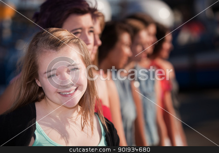 Smiling Female Youth in Group stock photo, Smiling blond teenage girl in front of group by Scott Griessel