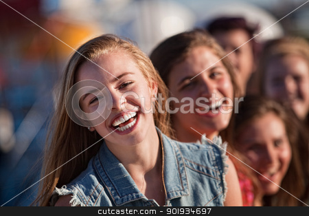 Young Blond Girl Laughing with Friends stock photo, Blond teenager with friends laughing outdoors by Scott Griessel