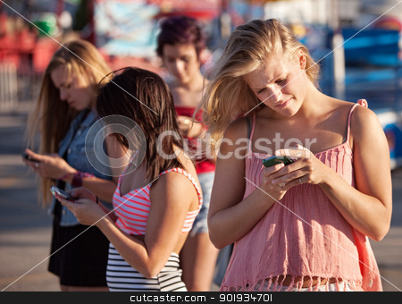 Serious Teenagers on Smartphones stock photo, Four female teenagers using their phones outside by Scott Griessel
