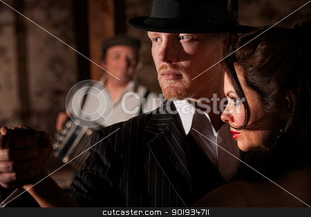 Tango Dancers Looking Ahead stock photo, 1920s style Tango dancers looking ahead with bandoneon player in background by Scott Griessel