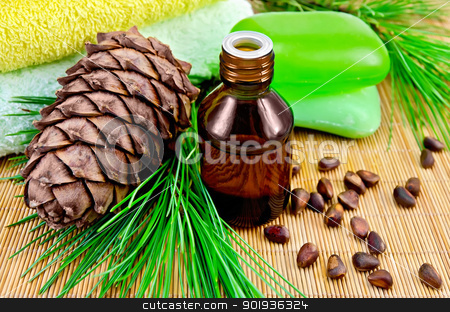 Oil cedar with pine cones and soap stock photo, Cedar oil in a bottle, with a branch of cedar cones, cedar nuts, two green soap, two towels on a bamboo mat by rezkrr
