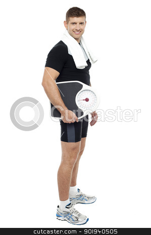 Full length portrait of young male carrying weight scale stock photo, Full length portrait of young male carrying weight scale isolated against white background by Ishay Botbol