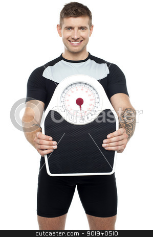 Smart young fit male showing weighing machine stock photo, Smart young smiling fit male showing weighing machine to camera by Ishay Botbol