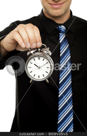 Business executive holding alarm clock. Cropped image stock photo, Business executive holding alarm clock over white background. Cropped image by Ishay Botbol