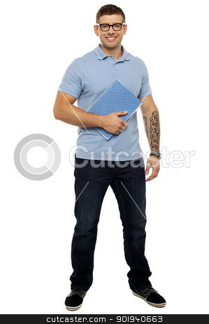 Casual young guy holding notebook stock photo, Full length portrait of casual young guy holding notebook by Ishay Botbol