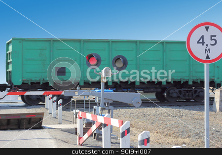 railroad cars at the crossing with a barrier  stock photo, railroad cars at the crossing with a barrier and a red traffic light. by aarrows