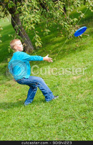 Little boy playing frisbee stock photo, Little boy playing frisbee on green grass by nvelichko