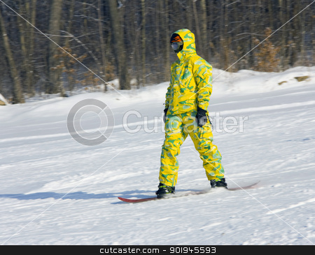 Snowboarder in a yellow suit  stock photo, Snowboarder in a yellow suit going from mountain on against wood by aarrows