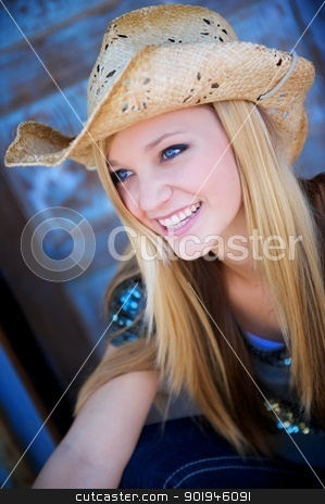 Attractive Blond Model Smiles While Wearing Cowboy Hat stock photo, Attractive Blond Model Smiles While Wearing a Tattered Old Cowboy Hat by Shane Morris
