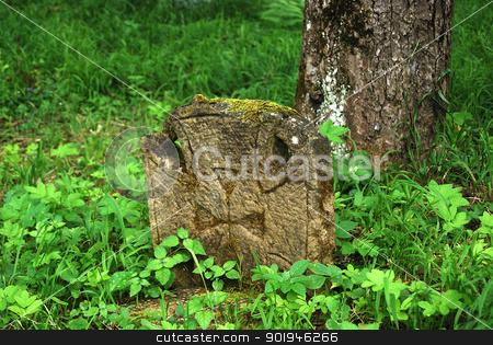 Christian tombstone in forest  stock photo, Old christian tombstone in forest meadow and tree  by Aleksandar Varbenov