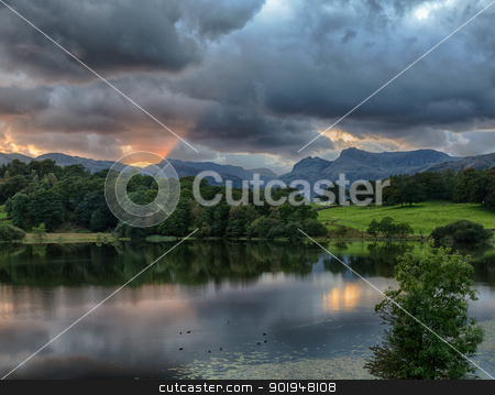 Sunset at Loughrigg Tarn in Lake District stock photo, Sun setting over Langdale Pikes with Loughrigg Tarn in foreground by Steven Heap