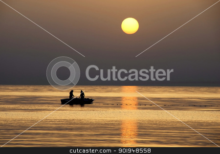 Fishing at sunrise stock photo, silhouettes of two fishermen fishing in boat on sea at gorgeous sunrise in Tunisia by Julija Sapic