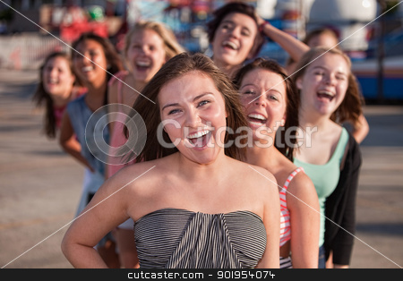 Laughing Teenage Friends  stock photo, Laughing teenage friends behind one another outside by Scott Griessel