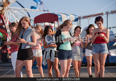 Teen Girls Text Messaging stock photo, Group of 8 teenage girls text messaging at an amusement park by Scott Griessel