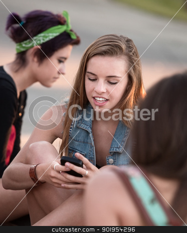 Cute Teen Girls Using Phone stock photo, Cute blond teenage girl using her cell phone by Scott Griessel