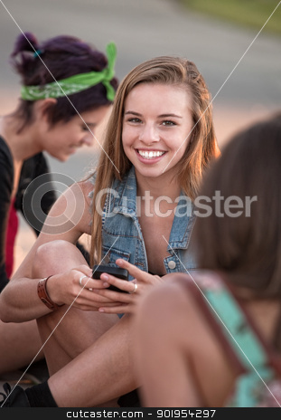 Cute Teen With Phone stock photo, Cute European teenage girl sitting on ground with phone by Scott Griessel