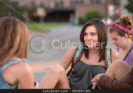 Teen Girls Sitting Outside stock photo, Pretty young teenage girls sitting on the sidewalk talking by Scott Griessel