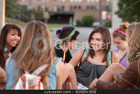 Young Woman Laughing with Friends stock photo, Young woman laughing with her friends sitting outside  by Scott Griessel