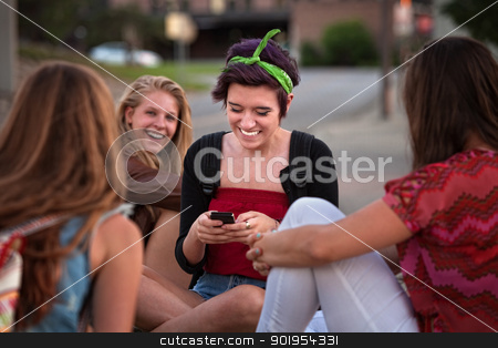Hispanic Teen with Friends and Phone stock photo, Teenager and friends playing with a cell phone by Scott Griessel
